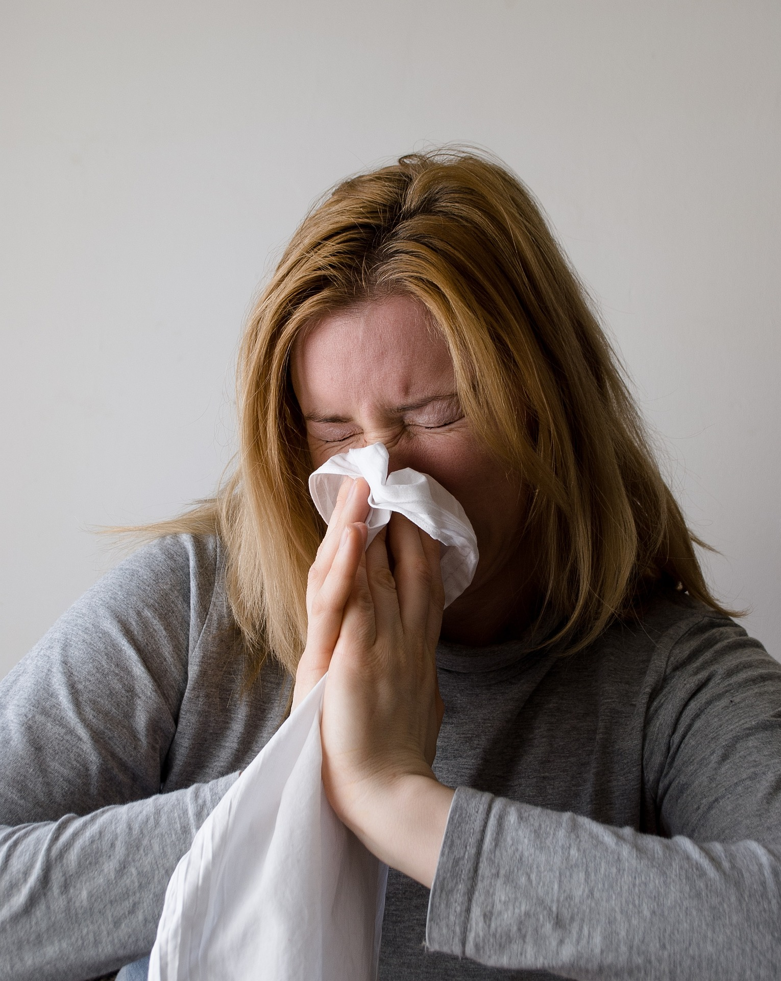 woman suffering from allergens with windows