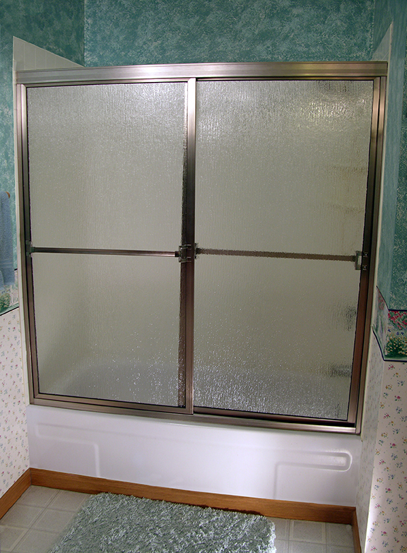 framed tub enclosure with sliding door and decorative glass