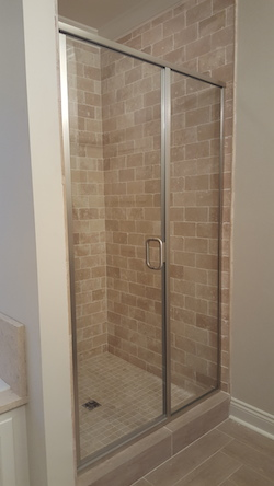 swinging glass shower doors with arched top and decorative glass