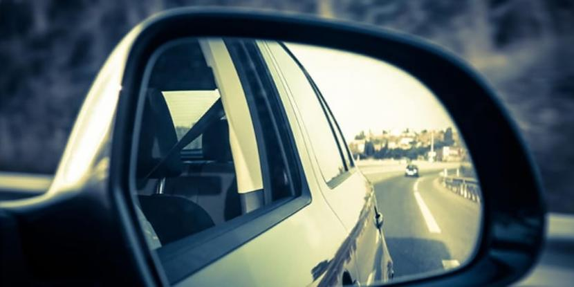 a car's side mirror reflecting the road behind the car