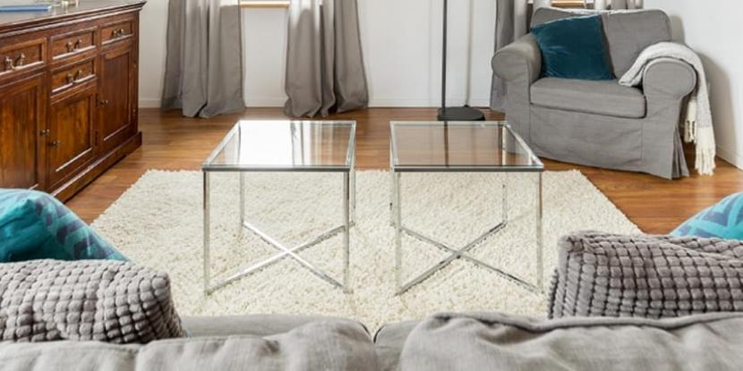 Two side tables in the middle of a living room with glass tabletops