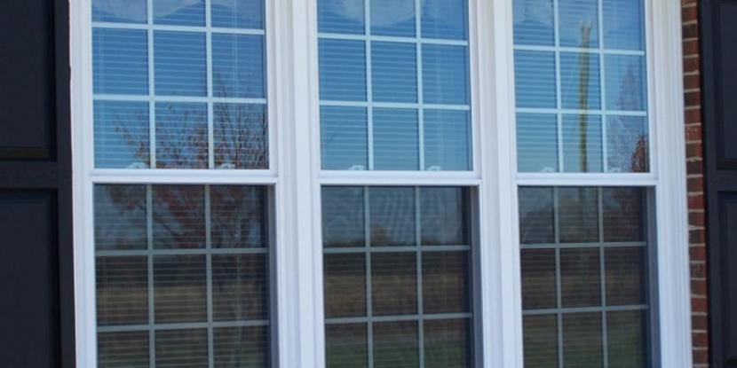 Three double hung windows with black shutters