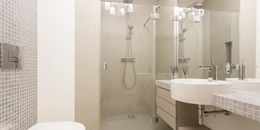 A bathroom with a glass shower door