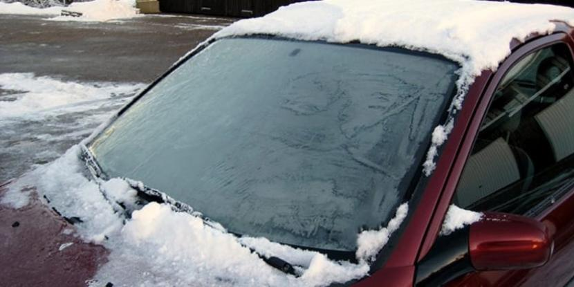 A car covered in snow with a frosted windshield