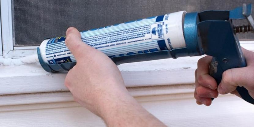A man sealing a window with caulk