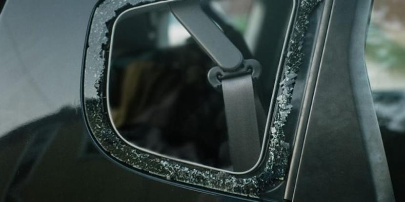 A car side mirror with a shattered glass mirror