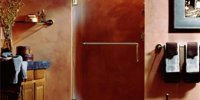 A glass shower door with a bar handle