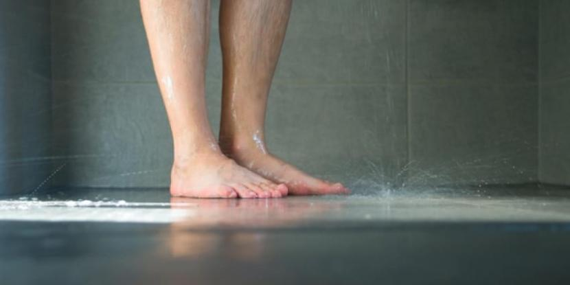 The floor of a shower while a person is showering.