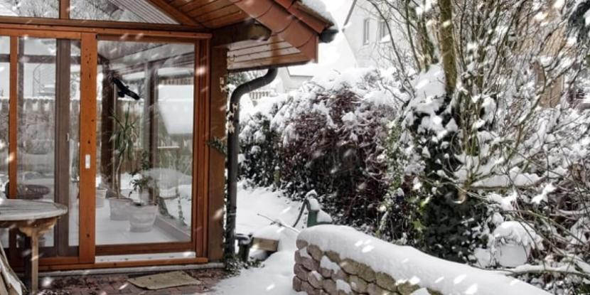 An outdoor view of a sunroom on a snowy winter day