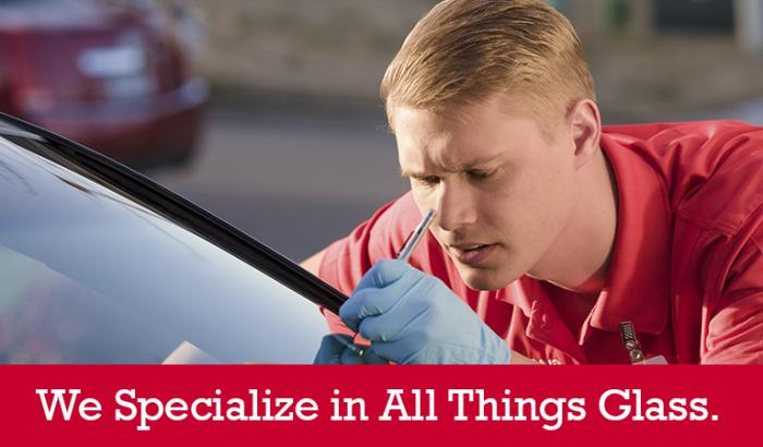 "Closeup of a Glass Doctor specialist repairing a crack in a windshield with ""We Specialize in All Things Glass"" written below it"