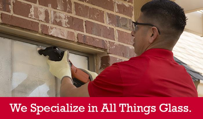 "Glass Doctor specialist repairing a home window seal with ""We Specialize in All Things Glass"" written below it"