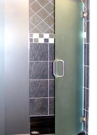 frameless shower door with thick smokey glass swinging door